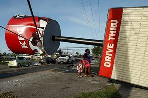 People walk under a Kentucky Fried Chicken sign blown over by Hurricane Matthew in the Bahamas capital