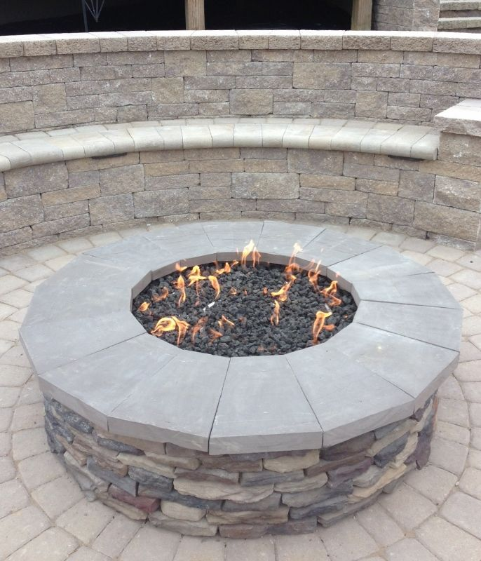 Gas firepit with stone veneer and natural stone caps. Seating wall behind.