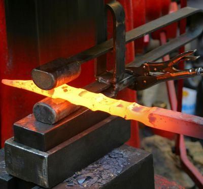 Spring fuller. Fullering (spreading or reducing) with a power hammer and tongs, approximately 1800°F