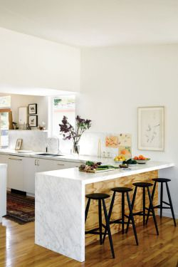 bright hard wood floor, black bar stools + white marble kitchen counter top
