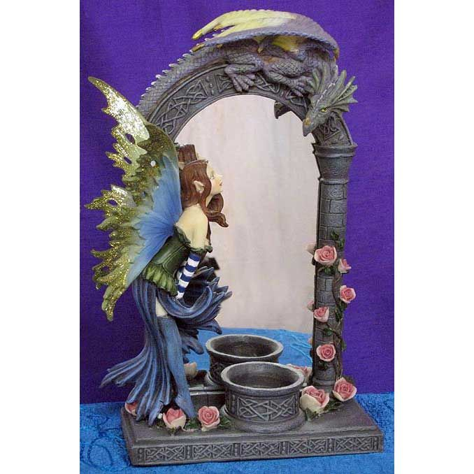Fairy Candleholder Mirror with Dragon. This pretty ornamental fairy mirror would make a lovely addition to a sideboard or dresser! Adorned with glitter and rosebuds, the fairy stands on tip-toe in conversation with a curious dragon. Place a lit tea-light candle in the holder and let the mirror reflect the glow around the room. Lovely details and colours!