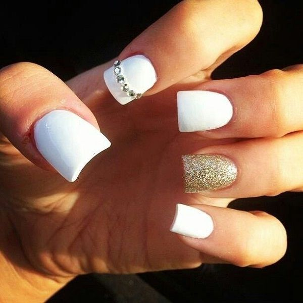 Simple and beautiful white and gold nail art design. The nails are painted in white nail polish as base and gold glitter polish on top with silver beads as well.