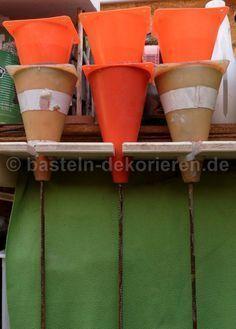 Zwei ineinander gesteckte Straßenhütchen, von denen das untere mit Beton gefüllt…