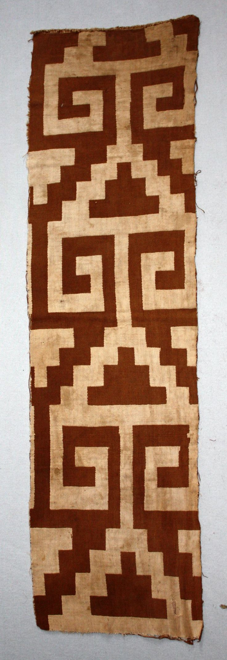 Textile fragment; cotton; double weave with paired wefts; large scale geometric design - stepped triangles with two angular scroll appendages; linked; edging down one warp selvedge; brown and cream.