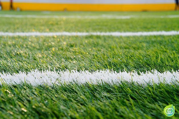 Vista a detalle al pasto sintetico deportivo en campo de futbol, realmente parece natural.