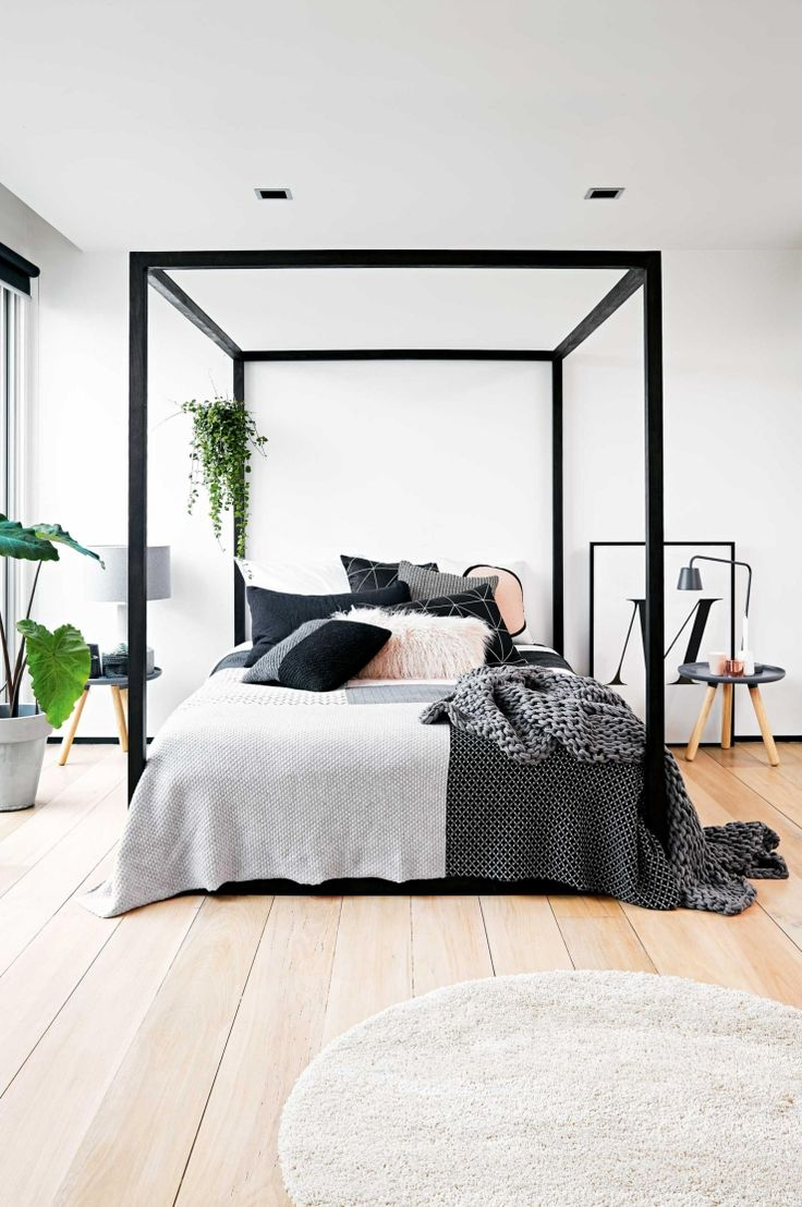 Black four-poster bed, grey and black bed linen, extra long timber  floorboards, indoor plants, square black downlights