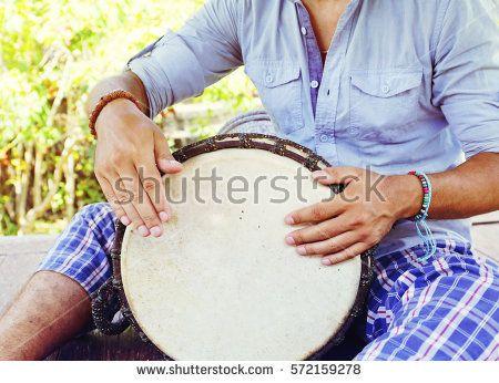 man playing on djembe