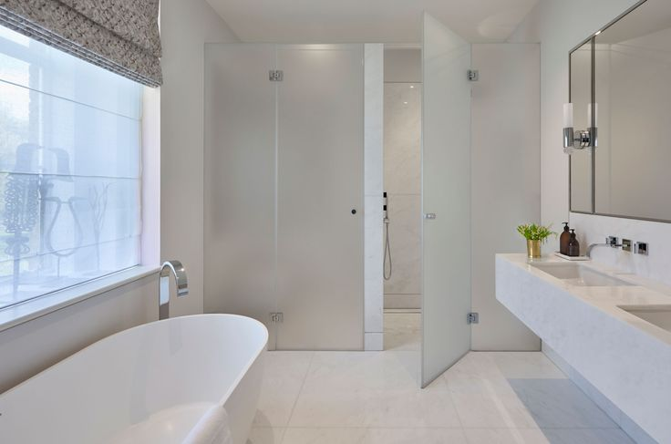 Clean design with no visible tile lines just expanses of surface - and no door frames - clean lines.  white and neutral. Lots of natural light.  frosted glass frameless walk in shower door. Double wall hung basin. wide mirror.  Simple taps. Another pristine bathroom from Helen Green - Family House, Chelsea