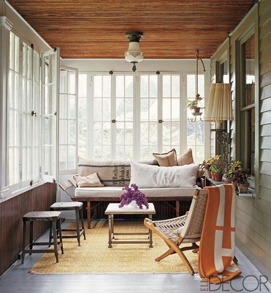 Wood-frame windows enclose the front porch of the Columbia County, New York, cottage shared by designer Dale Saylor and stylist Joe Williamson. A 19th-century folding bench is topped with pillows covered in antique grain sacks, and the Czech wood-and-fabric chair is from the 1950s.