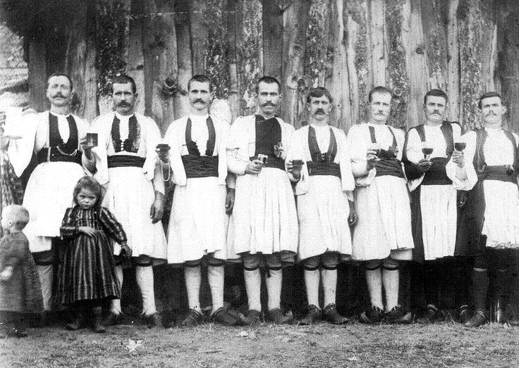"""Συλλογική φωτογραφία, η οποία απεικονίζει άνδρες από τη Σμίξη, Γρεβενών να κρατούν στα χέρια τους γεμάτα ποτήρια. Αναμεσά τους διακρίνονται και μικρά παιδιά. Η φωτογραφία έχει τραβηχτεί στις αρχές του εικοστού αιώνα. Ασπρόμαυρη ψηφιοποιημένη φωτογραφία, στης οποίας το πάνω μέρος της δεξιά αναγράφονται τα εξής:""""{δασανάγνωστη λέξη}MANAKIA Fotografi { δύο δυσανάγνωστες λέξεις}"""
