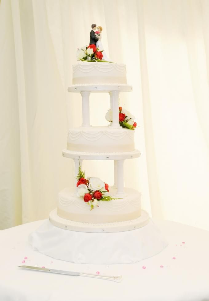 Kake i tre etasjer med roser og brudepar på toppen  http://kakene.no