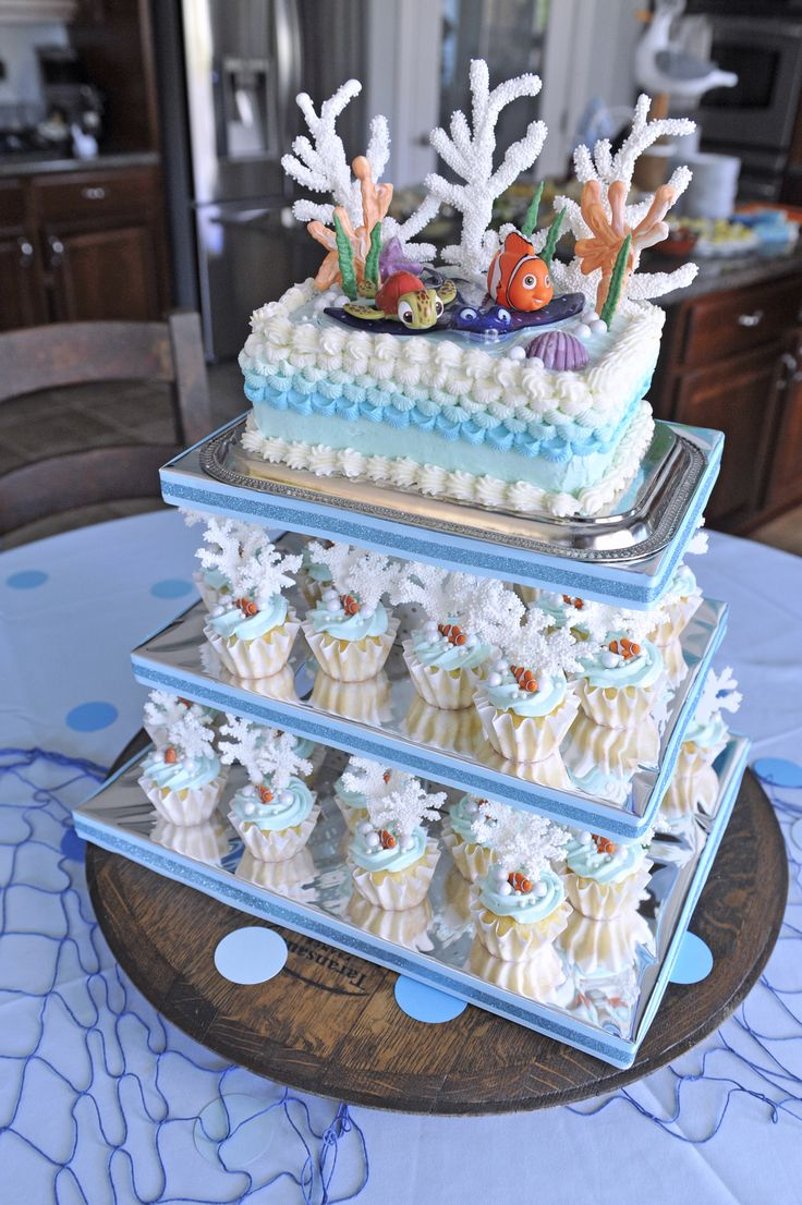 Finding Nemo Birthday Party   Smash Cake and Cupcake Stand   Tropical cupcakes with white chocolate buttercream frosting, decorated with Nemo, chocolate coral, and candy pearls   Cake stand constructed from wood, silver paper and ribbon