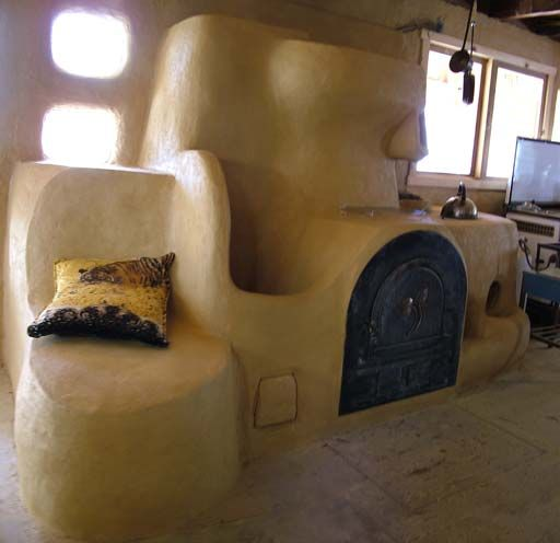 Beautiful example of a wood-fired rocked stove used for cooking and heating. This has a stove-top, oven, heated bench, and wood drying spot incorporated.