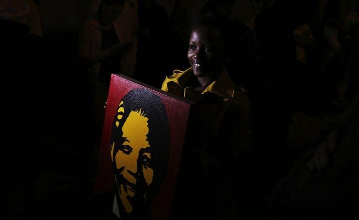 Per Madiba Una donna solleva un poster di Nelson Mandela fuori dalla sua casa a Houghton, Sudafrica.  (Reuters/Siphiwe Sibeko)
