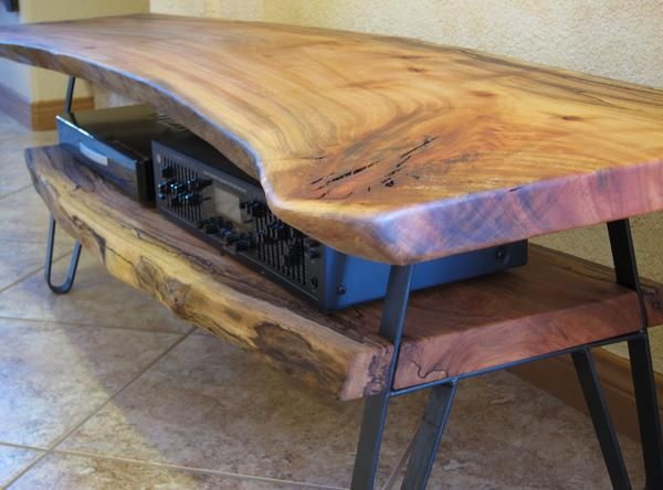 This log TV stand was made from solid Avocado wood and has raw steel legs.