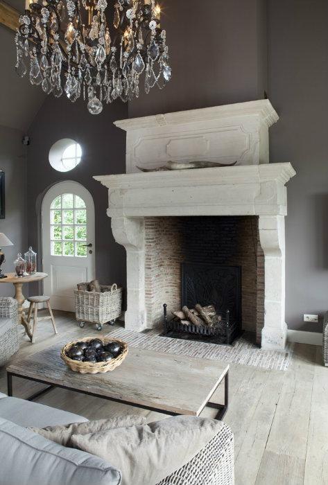 Bourgondisch Kruis Designs | Grand fireplace, greige décor and stunning chandelier