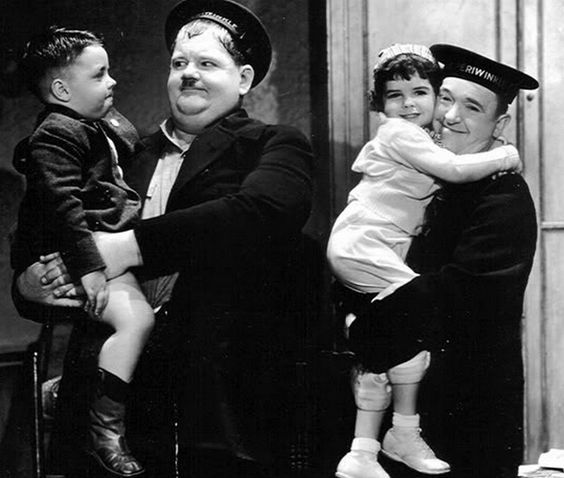 Stan and Ollie playing around on the set, with Our Gang kids Spanky McFarland and Darla Hood.