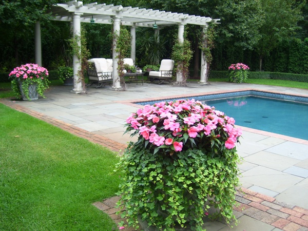 A pergola defines a gorgeous seating area in this classically-beautiful landscape by David J Frank Landscaping in Germantown, WI.