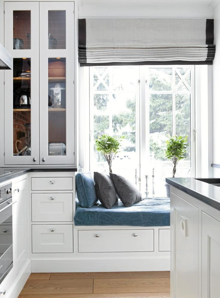 Innredningen fra Lidhults utnytter hver millimeter i det romslige kjøkkenet. Til høyre for sittebenken er det doble dører ut til terrasse og hage. Liftgardiner i linstoff fra Designers Guild. Teppe og puter fra Day Home.
