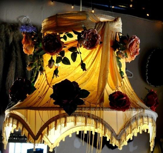 scarf and fake roses draped over a lamp shade
