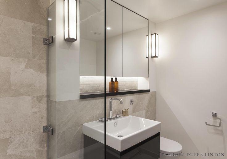 Bespoke dark wood and mirrored cabinet in master bathroom. Catalano sanitaryware and Inova vanity unit. Deck-mounted Hansgrohe taps. #GD&LBespoke