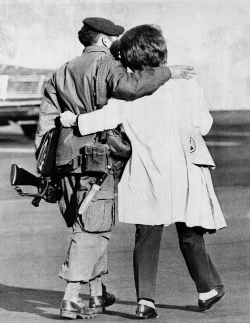 This Green Beret soldier clutches his M-16 rifle as his wife clutches him, just after some 102 members of a Green Beret commando raiding party returned to Ft. Bragg, Carolina on Wednesday, Nov. 25, 1970. The raiding party went into North Vietnam in an unsuccessful attempt to free American prisoners of war. / Credit: AP Photo