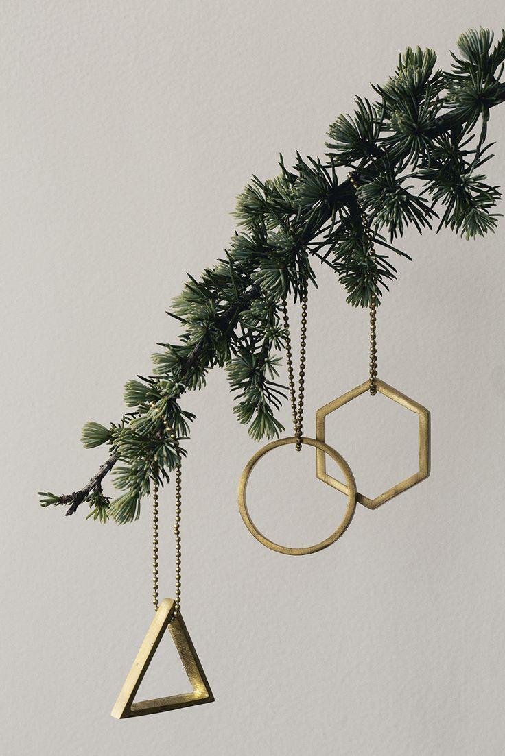 Gold geometric ornaments on Christmas tree branch