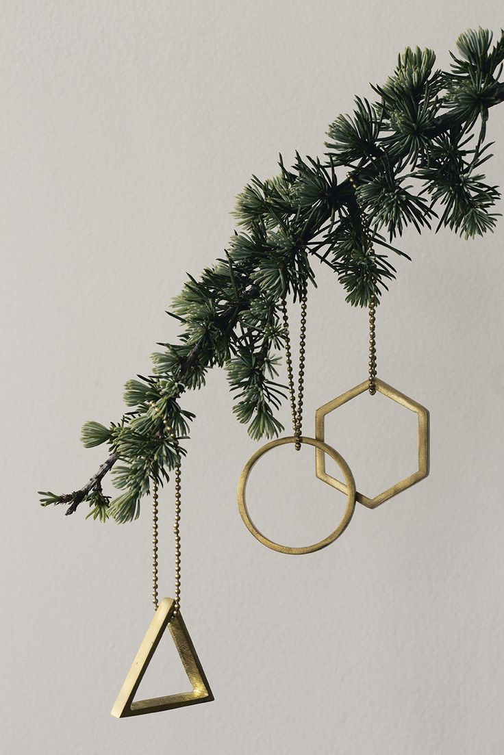 Gold geometric ornaments on Christmas tree branch
