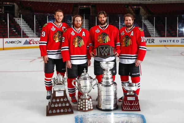 Jonathan Toews, Duncan Keith, Brent Seabrook and Patrick Sharp pose with the trophies.