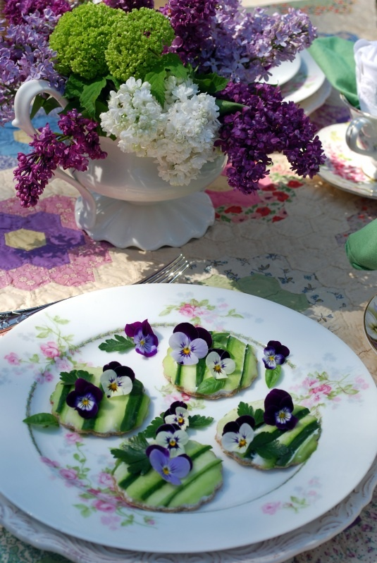 open faced cucumber sandwiches are decorated with edible violas along with parsley  basil