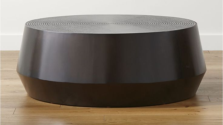 Udan Round Coffee Table Crate & Barrel Mahogany coffee table centers the room with its warm coffee color and global, marketplace feel. Handcrafted by skilled artisans, each tabletop is chiseled with rustic, concentric circles in contrast to the table's sleek, drum-like form.