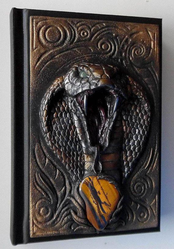 È un taccuino unico con copertura a mano polimero argilla - King Kobra con pietra di occhio di tigre naturale. Notebook ha 98 fogli bianchi (Canson Art Book One). Si potrebbe usarlo come giornale o diario o sketchbook.  Se cercando dono straordinario - troverete :-)  Formato: A6. Dimensioni: 10,8 x 15,8 cm.