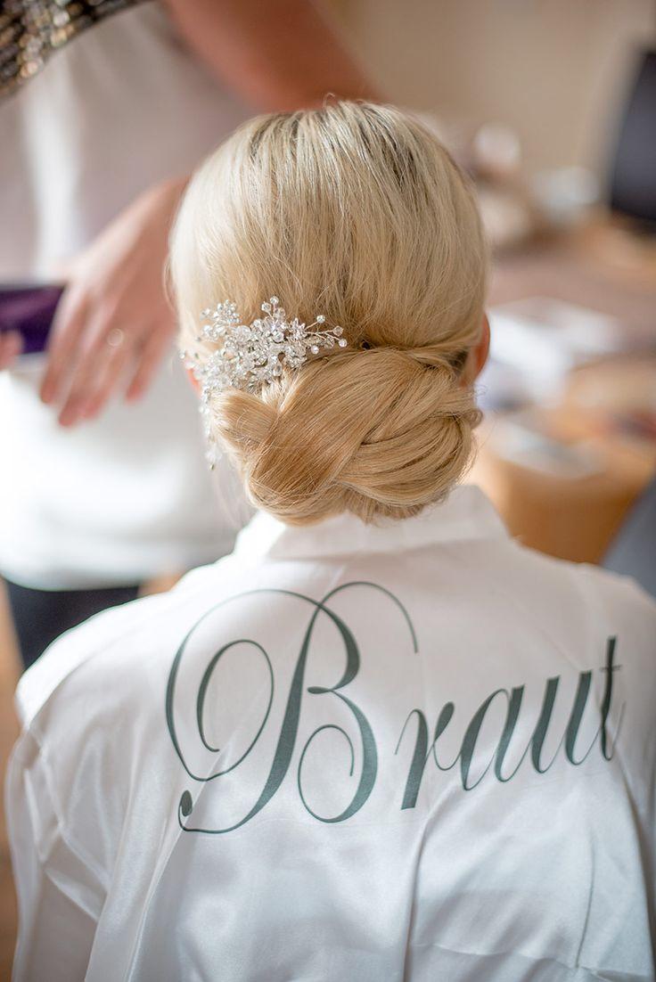 Die Braut im personalisierten Morgenmantel mit ihrem hübschen Haarschmuck. Die Brautfrisur für Ihre Hochzeit ist toll oder? Foto: Jennifer & Thorsten Photography