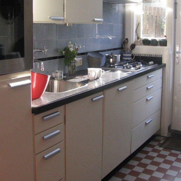 Jaren 30 keuken Piet Zwart met bijpassende wandtegels met zwarte strip en geblokte vloertegels