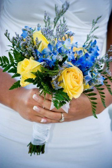 Bright yellow roses contrast beautifully with bright blue delphinium and surrounded by feathery limonium