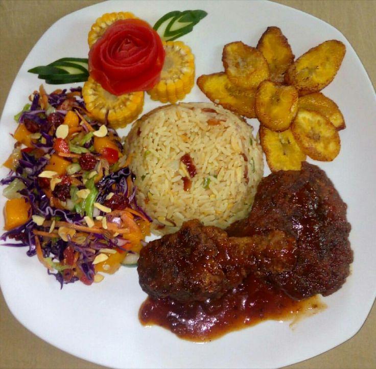 Pollo en reducción de coulis de pimientos y vino tinto. Acompañado de arroz al curry, ensalada con vinagreta de fresas y uvas pasas, plátanos fritos y maiz al vapor