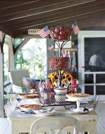 Put your pies on a pedestal for a dessert buffet on the porch — shown here, cake stands in vintage milk glass and clear glass. Blue-and-white transferware plates are the perfect backdrop for golden hand-crimped crusts. Build a festive centerpiece using tiered wire baskets. Fill with help-yourself treats like ripe fruit — as well as utensils. Rolled red, white, and blue bandannas can serve as napkins.   - CountryLiving.com