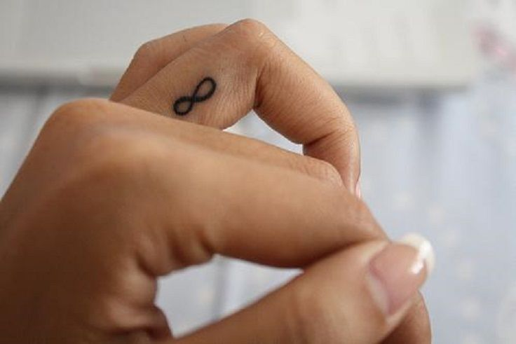 small infinity tattoo on finger