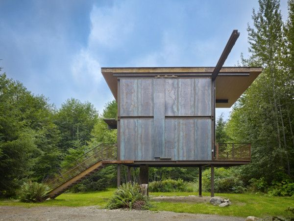 Cabin in Washington state sits on stilts to avoid nearby river flooding and was assembled off-site so that heavy machinery would not disturb nature.