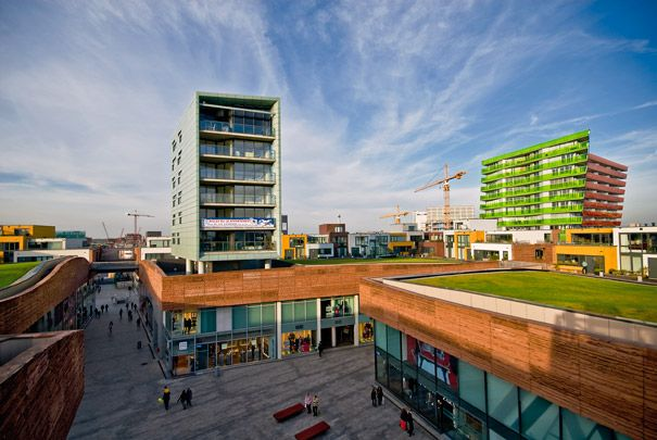 new centre of Almere is the Citadel shopping complex by the French architect Christian de Portzamparc. The principal square block of 130 by 130 metres is crossed by a pedestrian route and culminates in an artificial rolling landscape of grass-roofed shops dotted with family houses and an apartment complex.