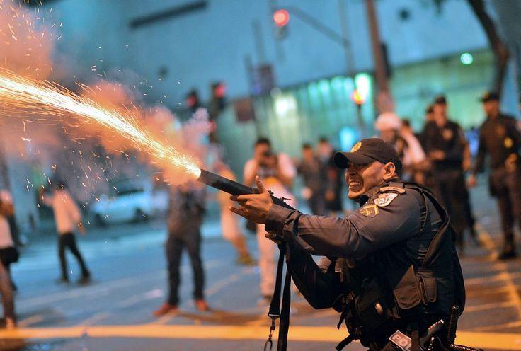 Un policía antidisturbios dispara gas lacrimógeno durante enfrentamientos con manifestantes de uniones sindicales en Rio de Janeiro (Brasil). (AFP/CHRISTOPHE SIMON/VANGUARDIA LIBERAL)