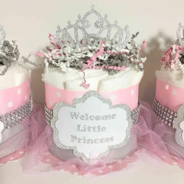 Gorgeous tutu diaper cake will wow all of your guest at your baby shower. Decorated with pink and gray ribbon with silver-toned rhinestones, this diaper cake se
