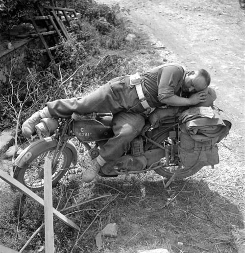 Lance Corporal Bill Baggott sleeps on his motorcycle in Falaise, France - 13 August 1944  Photo by Michael M. Dean