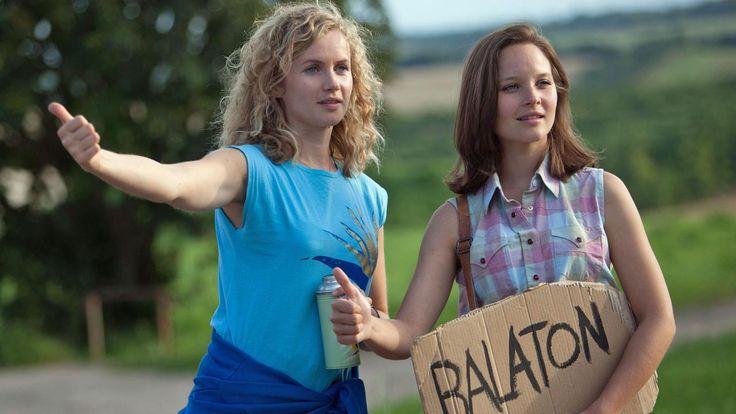 """""""Honigfrauen - 1. Urlaub im Paradies"""": Catrin Streesemann (Cornelia Gröschel) und Maja Streesemann (Sonja Gerhardt), die ein Pappschild mit der Aufschrift """"Balaton"""" in der Hand hält, heben ihren Daumen, um per Anhalter mitgenommen zu werden."""