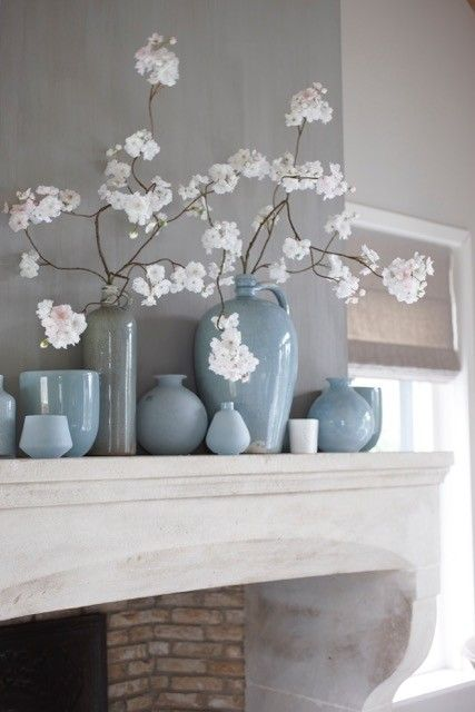 Blauwe vaasjes tegen een grijsblauwe muur voor een rustige en ruimtelijke…