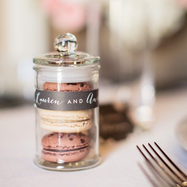 Mini glass jars full of macarons to give to your wedding guests
