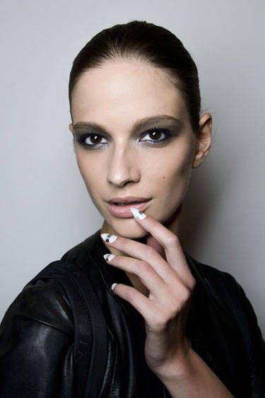Models were given long and sharply pointed white nails that were finished with a reflective silver racing stripe placed horizontally down the center.