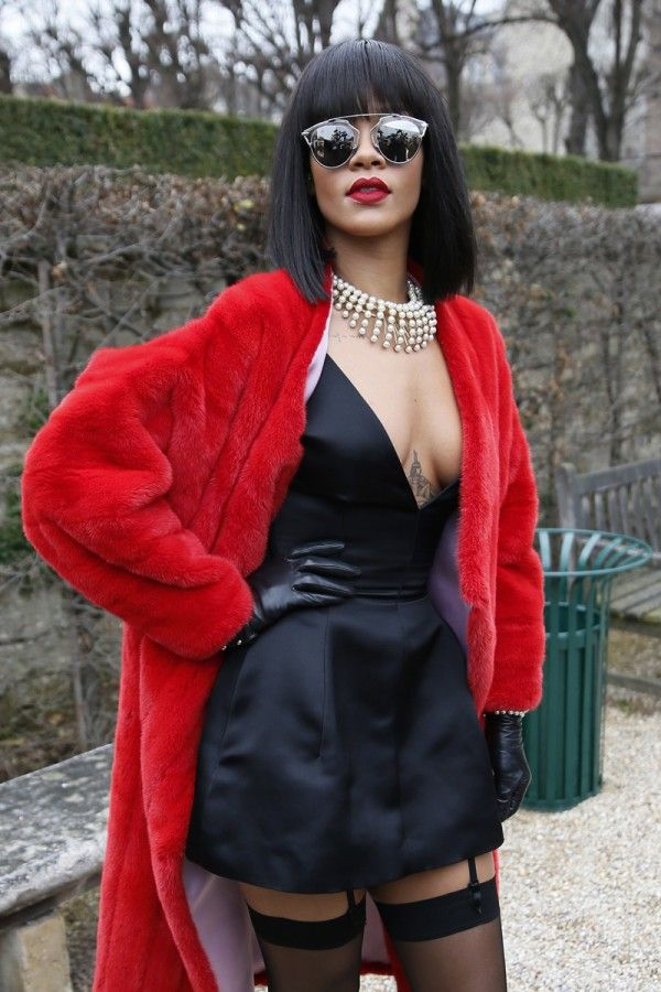"""Rihanna wore a Dior silk black dress and red stretched mink coat. She also wore a Dior  """"Mise en Dior"""" necklace and bracelet with gold finish and cream resin pearls, Dior sunglasses and Dior leather gloves."""