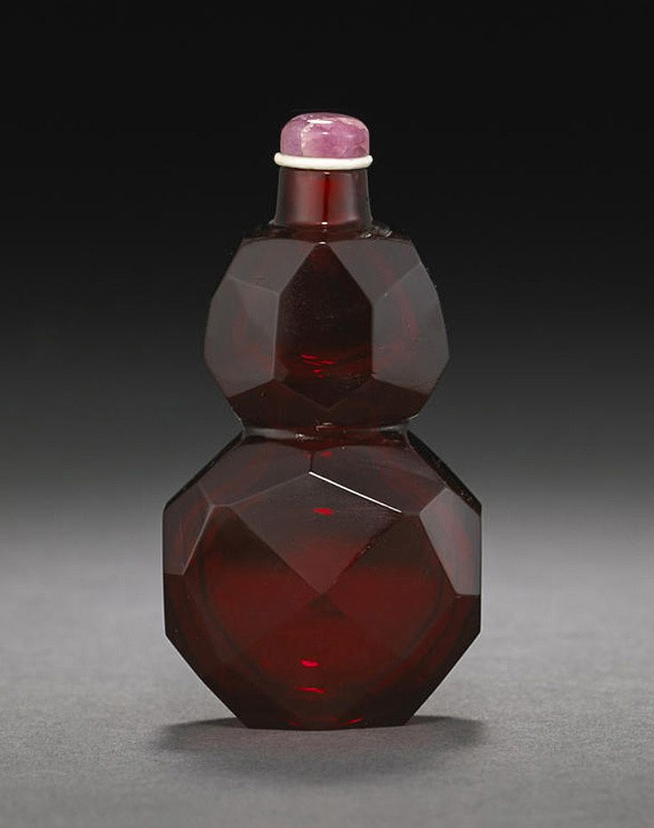 A fine ruby-red faceted glass snuff bottle Imperial, Palace Workshops, Beijing, 1730-1800. Well-hollowed, designed in the form of a double-gourd, carved overall with a symmetrical pattern of irregular facets. 2 1/2in (6.4cm)