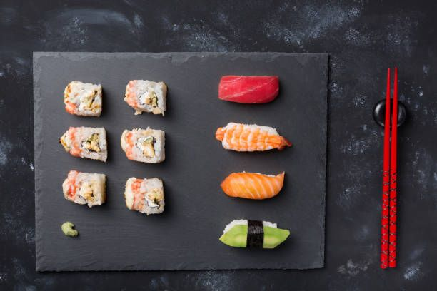 various sushi and rolls on slate plate and black stone table with